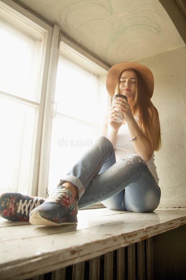Härlig ung kvinna i en cowboyhatt med koppen kaffe arkivbilder