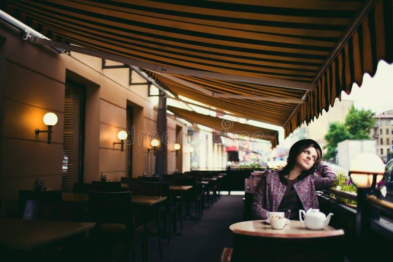 Härlig ung kvinna i en hatt med ett kopp tesammanträde i ett kafé som ser att förbigå för folk royaltyfria foton