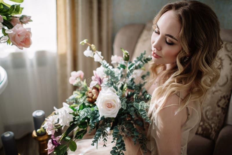 Härlig ung kvinna i en husklänning i budoar som dekoreras med härliga blommor som sitter på en vit säng med en markis, fas fotografering för bildbyråer