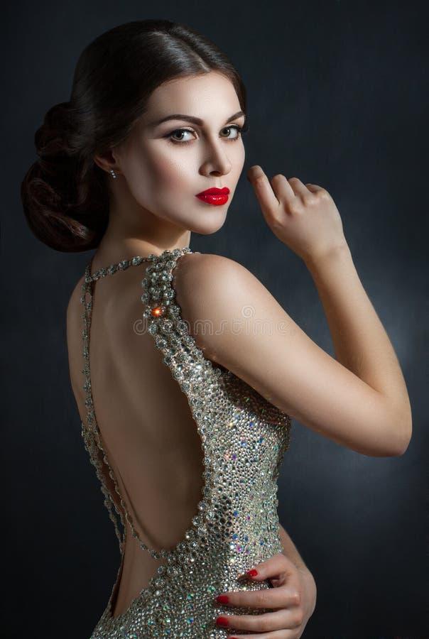 Härlig ung kvinna i en kristall för aftonklänning Perfekt skönhet, röda kanter, ljus makeup Blinka moussera stenar på klänningen arkivfoto