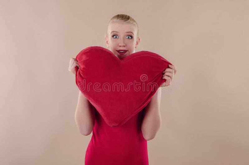 Härlig ung kvinna i en ljus röd åtsmitande klänning arkivbilder