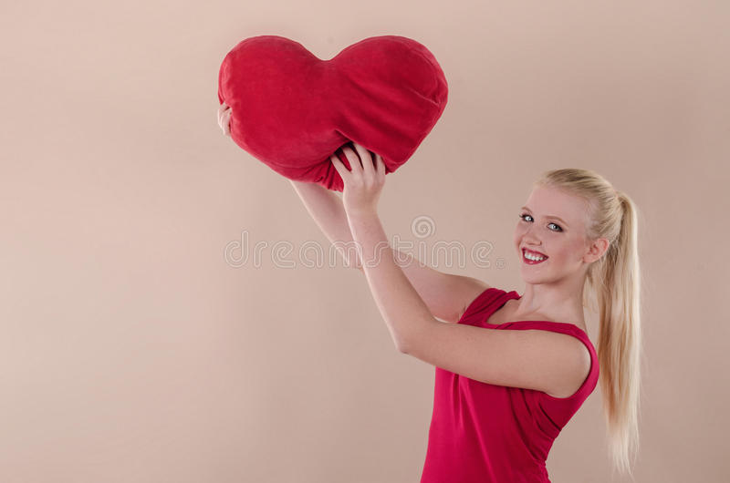 Härlig ung kvinna i en ljus röd åtsmitande klänning arkivfoto