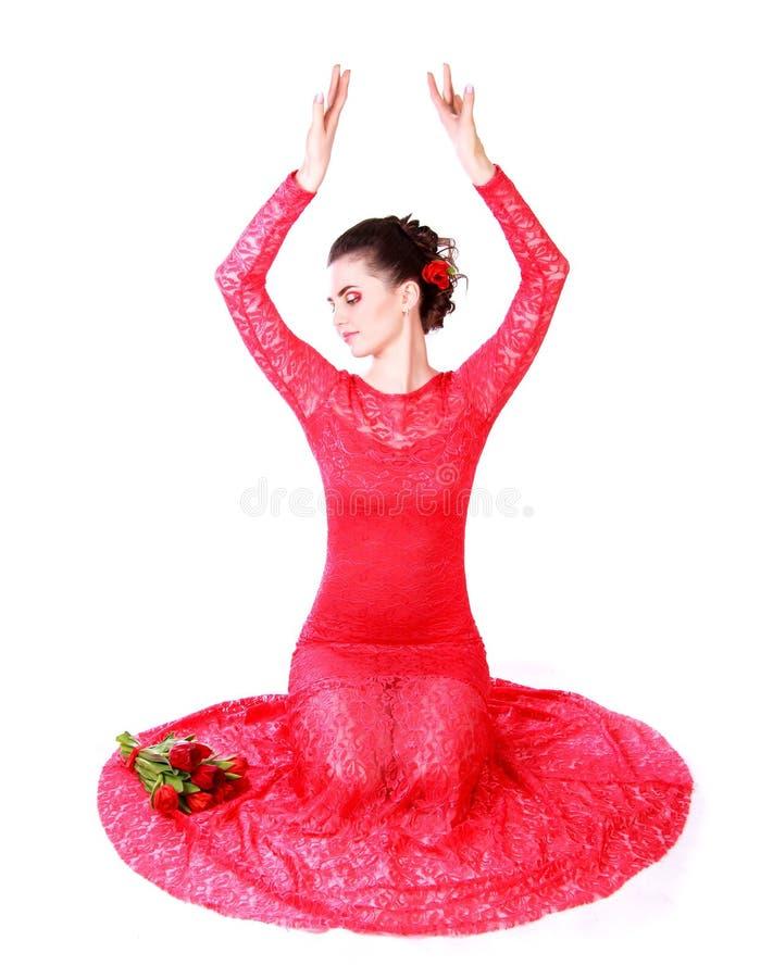 Härlig ung kvinna i en röd aftonklänning royaltyfri bild
