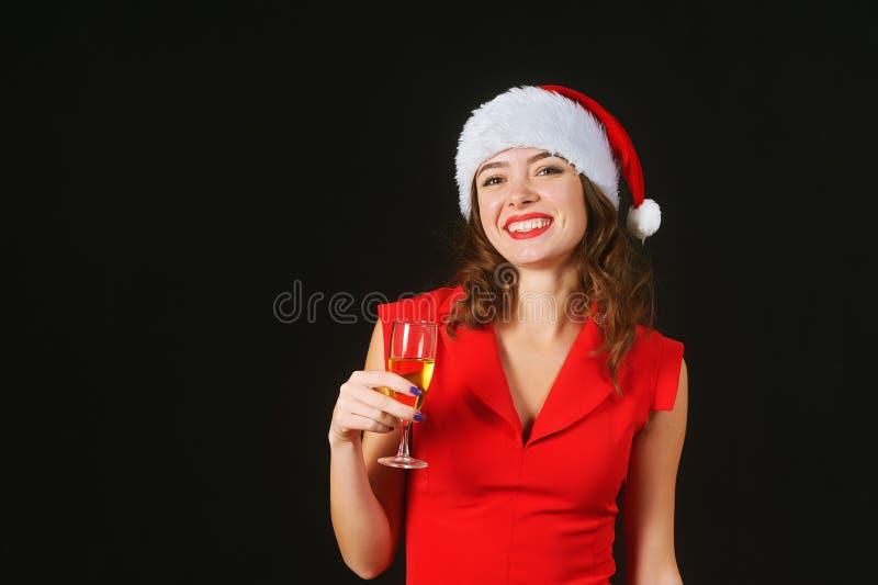 Härlig ung kvinna i en röd klänning och hatt av Santa Claus på en svart bakgrund royaltyfri fotografi
