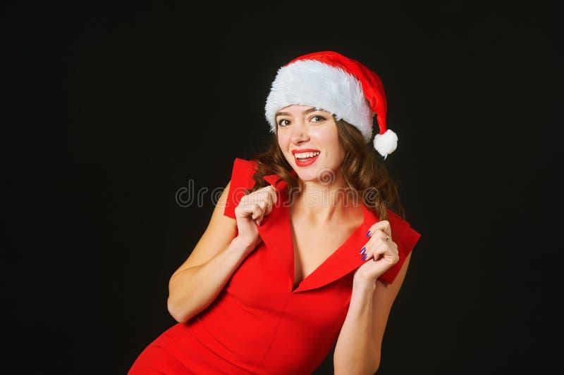 Härlig ung kvinna i en röd klänning och hatt av Santa Claus på en svart bakgrund royaltyfri foto