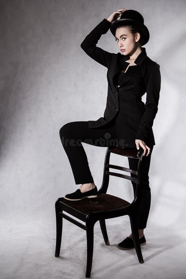 Härlig ung kvinna i en svart hatt och ett svart omslag arkivbild