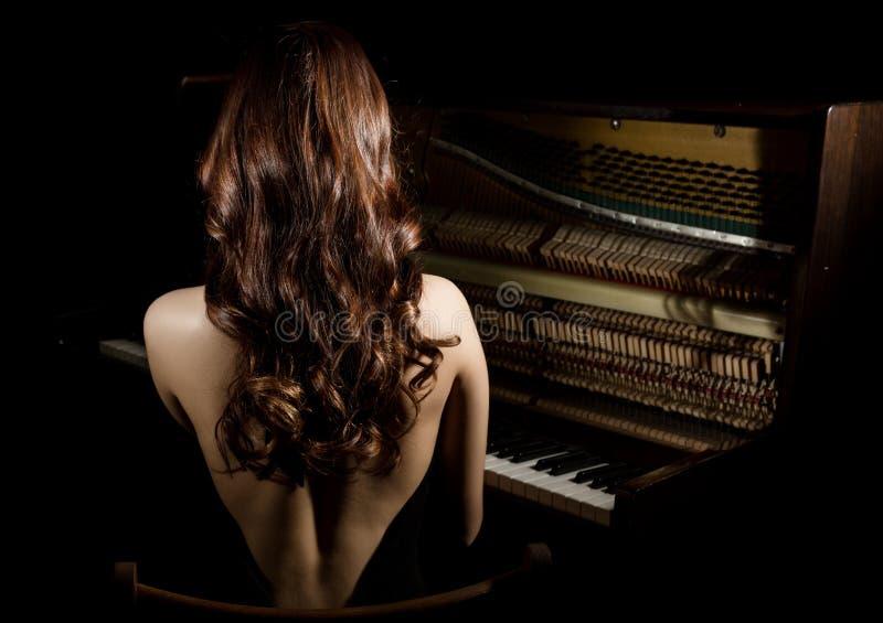 Härlig ung kvinna i en svart klänning med en öppen sittande tillbaka nere pianot på en mörk bakgrund arkivfoton