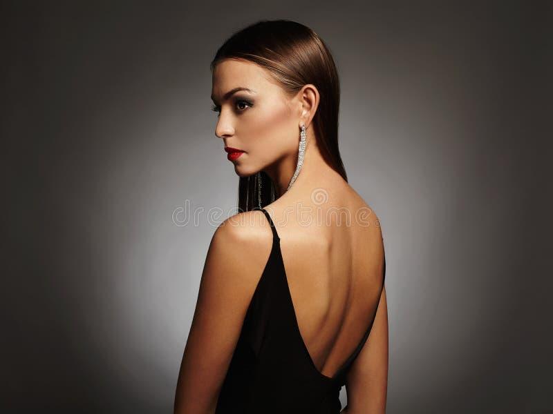 Härlig ung kvinna i en svart sexig klänning som poserar i studion, lyx skönhetbrunettflicka royaltyfria foton