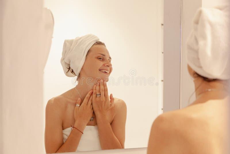 Härlig ung kvinna i en vit handduk i badrummet framme av spegeln, bruksskönhetsmedel Begrepp för hem- omsorg royaltyfria bilder