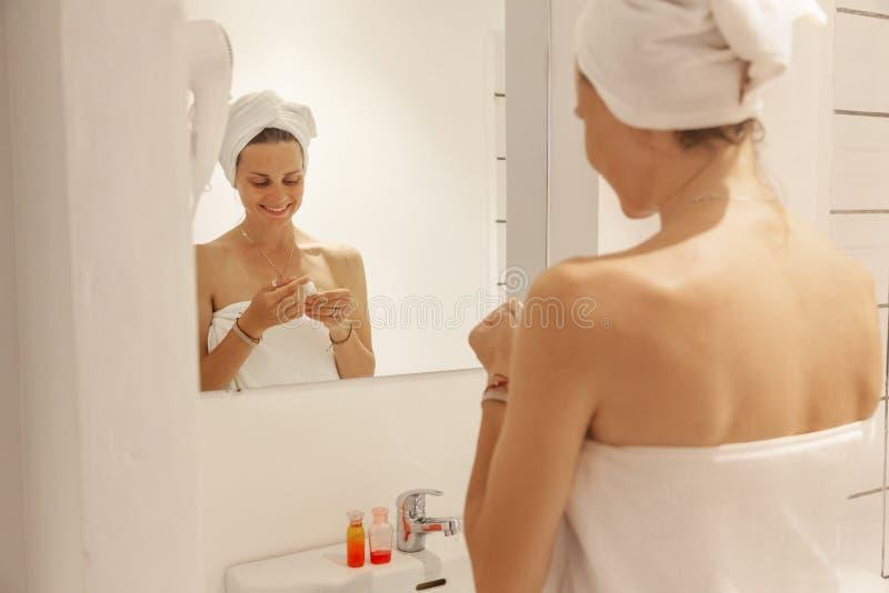Härlig ung kvinna i en vit handduk i badrummet framme av spegeln, bruksskönhetsmedel Begrepp för hem- omsorg royaltyfri foto