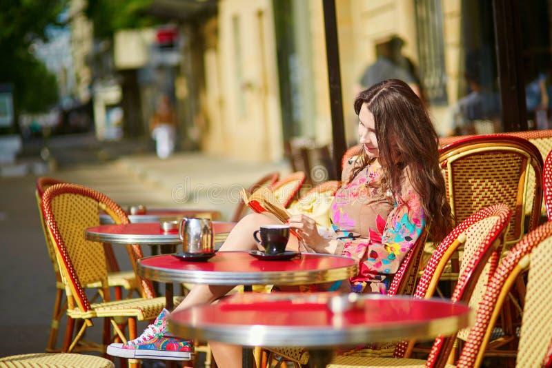 Härlig ung kvinna i ett parisiskt kafé royaltyfria bilder