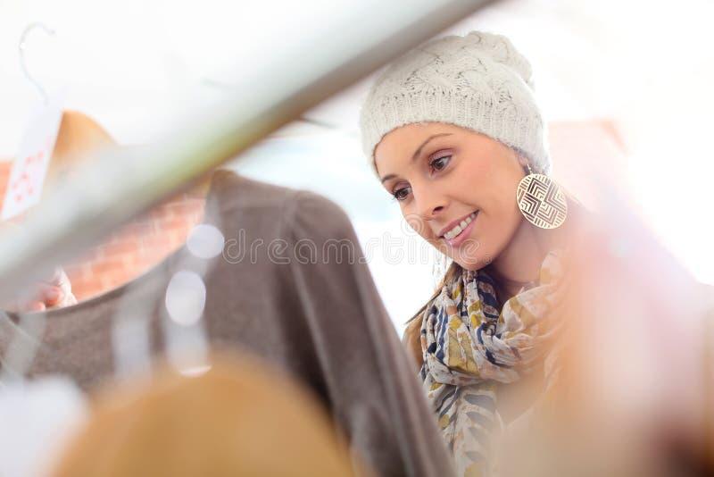 Härlig ung kvinna i ett shoppinglager som väljer kläder royaltyfri foto