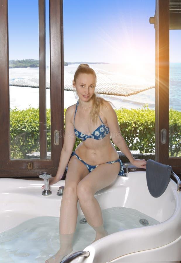 Härlig ung kvinna i ett stort hydromassagebadkar nära ett fönster som förbiser havet arkivbild