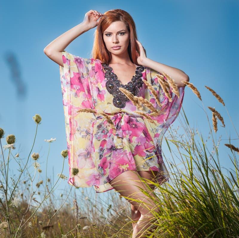 Härlig ung kvinna i fält för lösa blommor på bakgrund för blå himmel Stående av den attraktiva röda hårflickan med långt koppla a fotografering för bildbyråer