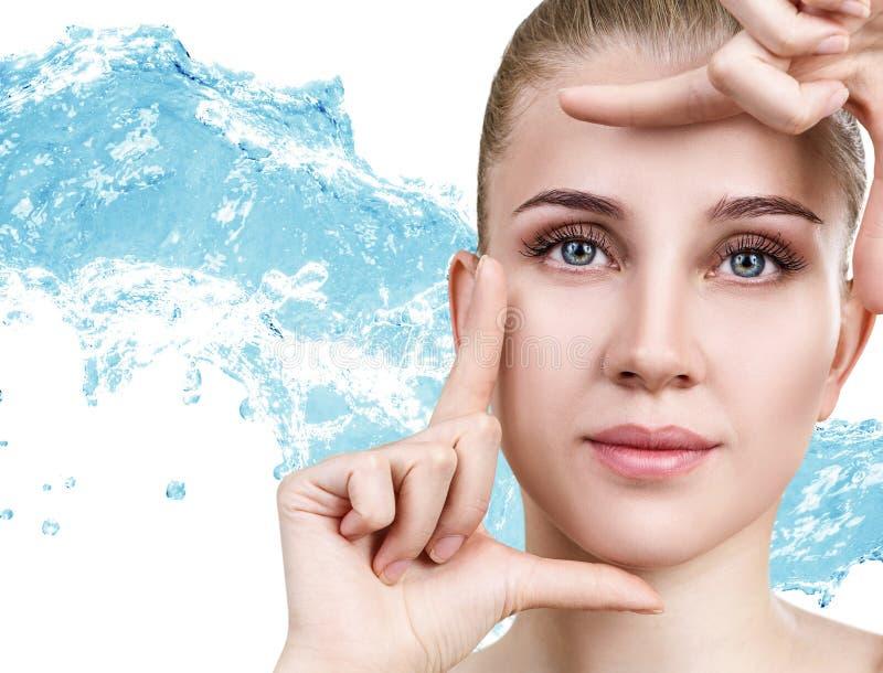 Härlig ung kvinna i färgstänk för blått vatten royaltyfria bilder