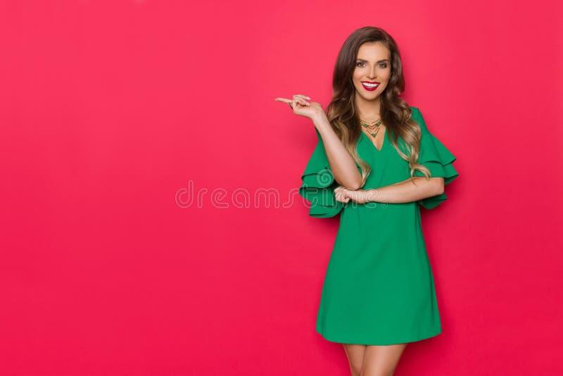 Härlig ung kvinna i grönt Mini Dress Is Smiling And peka royaltyfria bilder
