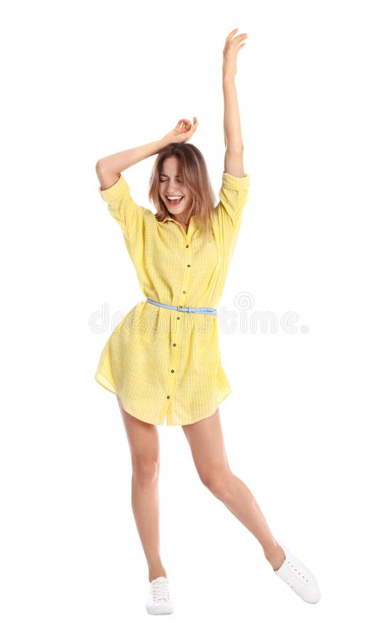 Härlig ung kvinna i gul klänningdans på vit arkivfoto