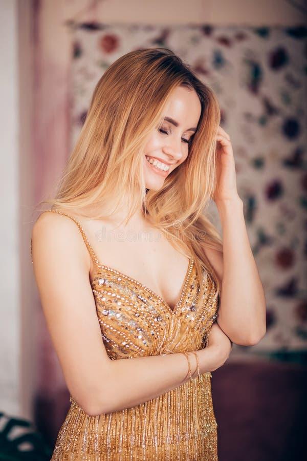 Härlig ung kvinna i guld- klänning som skrattar som inomhus ler arkivbilder