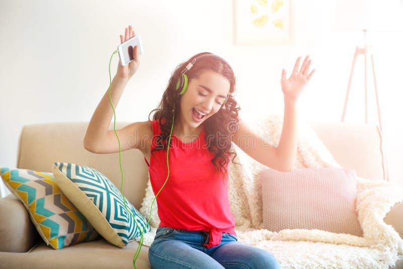 Härlig ung kvinna i hörlurar som hemma lyssnar till musik royaltyfria bilder
