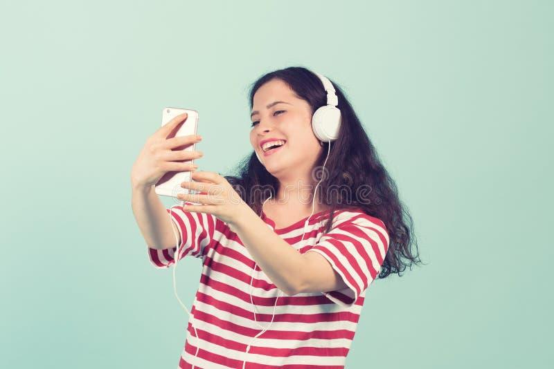 Härlig ung kvinna i hörlurar som lyssnar till musik och sjunger på färgbakgrund arkivfoto