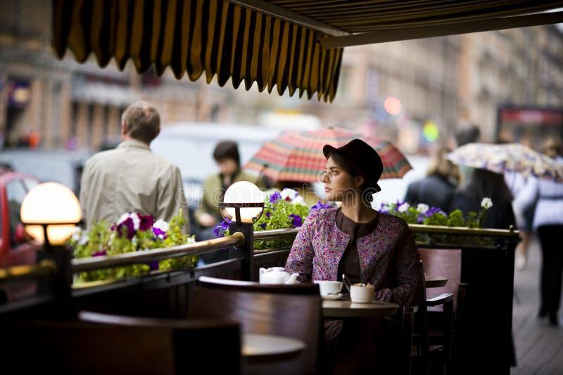 Härlig ung kvinna i hatt med ett kopp tesammanträde i ett kafé som ser prodasih av folk royaltyfria bilder