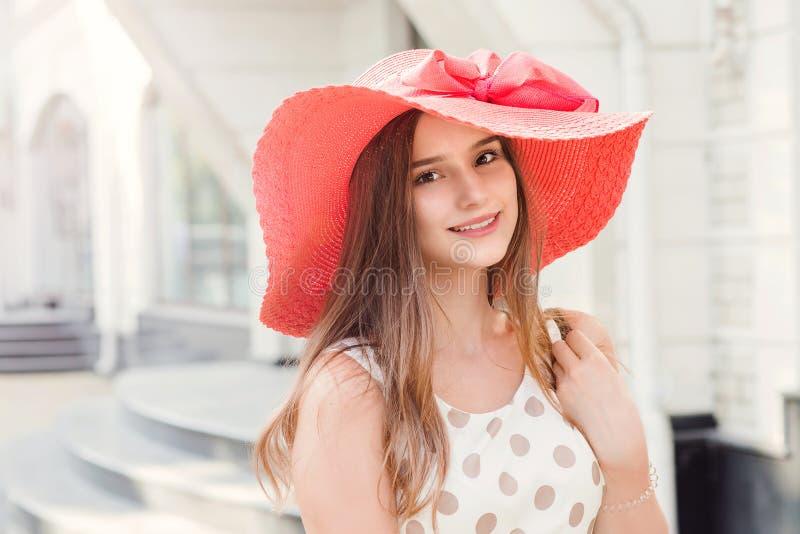 Härlig ung kvinna i hatt som går i staden som ler att se till kameran arkivbilder