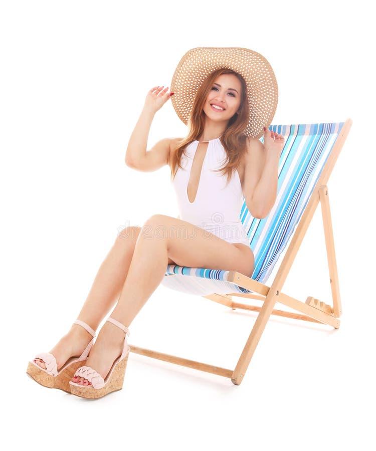 Härlig ung kvinna i hatt som kopplar av på chaise-vardagsrum, royaltyfri bild