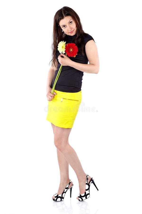 Härlig ung kvinna i kort gul kjol med gerberas, full kropp som framåtriktat vippar på hennes huvud royaltyfri foto