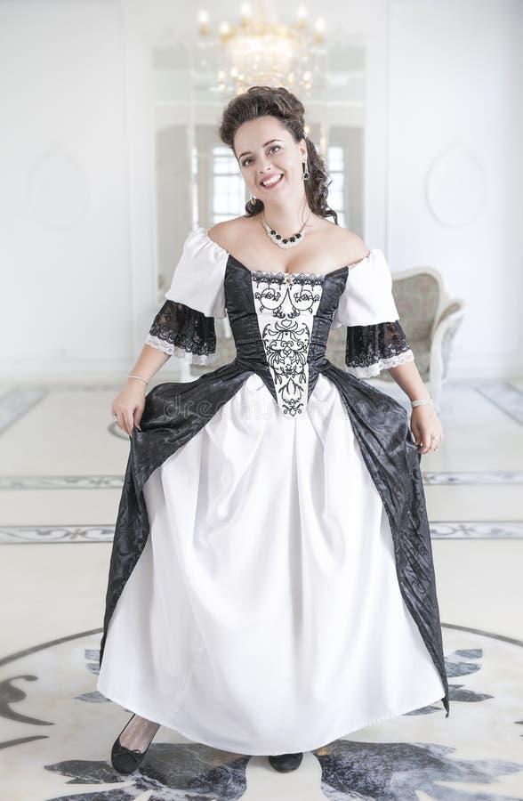 Härlig ung kvinna i lång medeltida klänningdanandecurtsey fotografering för bildbyråer