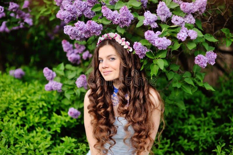 Härlig ung kvinna i lila blommor, utomhus stående royaltyfri fotografi
