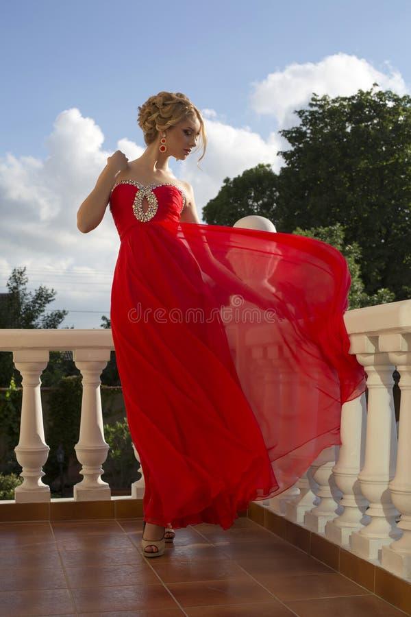 Härlig ung kvinna i lyxig röd klänning arkivfoton