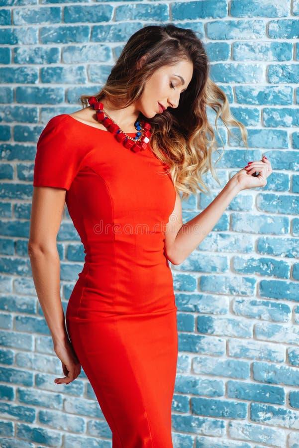 Härlig ung kvinna i röd klänning runt om blå bakgrund arkivfoto