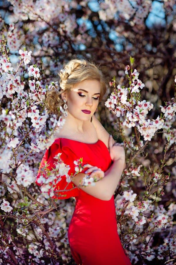 Härlig ung kvinna i röd klänning som tycker om lukten i en blomningvårträdgård arkivbilder
