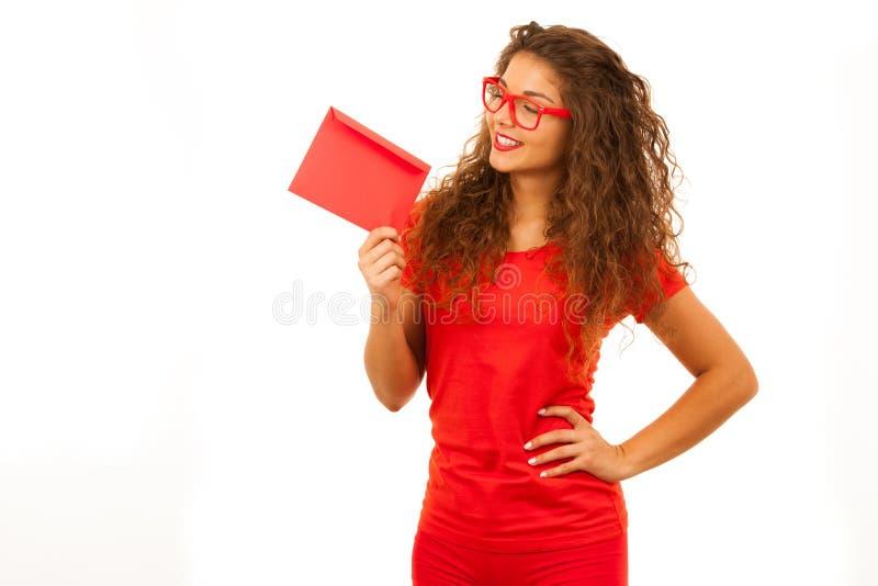 Härlig ung kvinna i rött hållande rött kuvert fotografering för bildbyråer