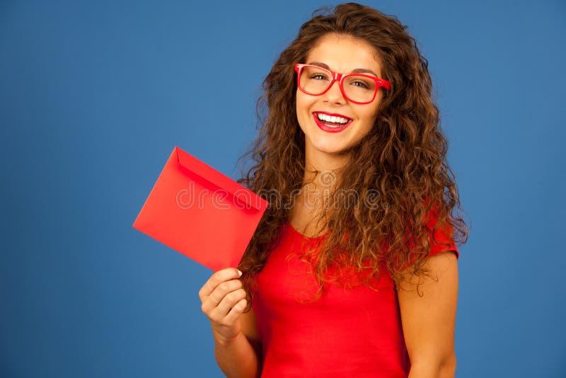 Härlig ung kvinna i rött hållande rött kuvert royaltyfria foton