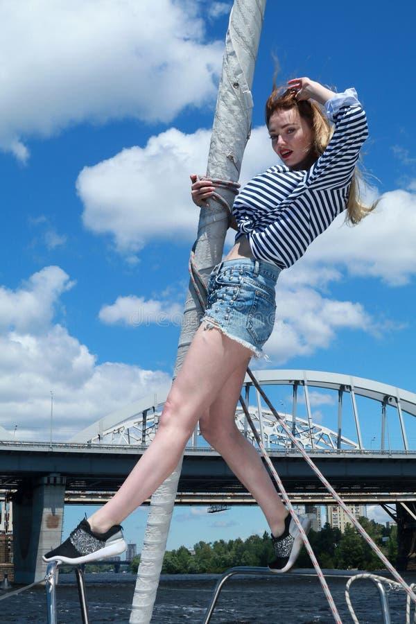 Härlig ung kvinna i randig kläder som står på yachten i solig sommardag arkivbilder