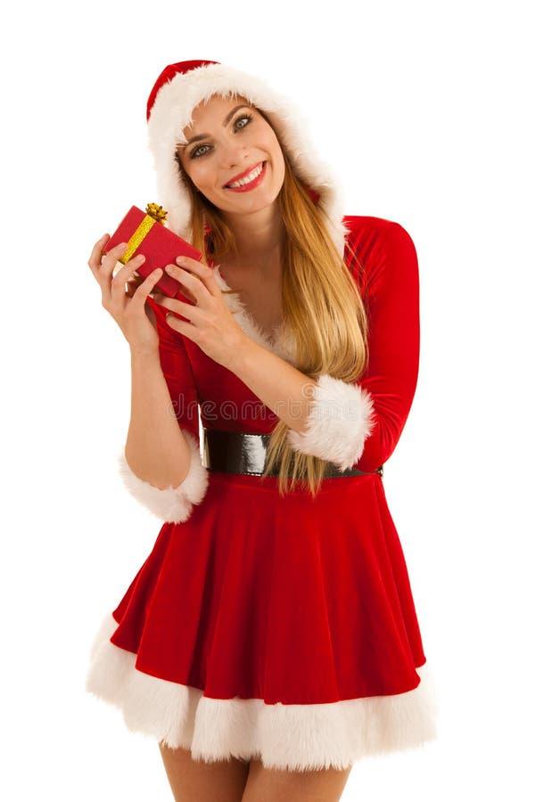 Härlig ung kvinna i Santa Claus klänningbärtråg för murbruk en närvarande isolat royaltyfria bilder