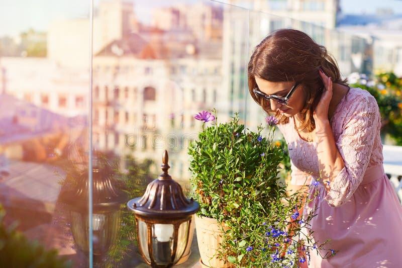 Härlig ung kvinna i solglasögon som luktar blommorna i kafé arkivbild