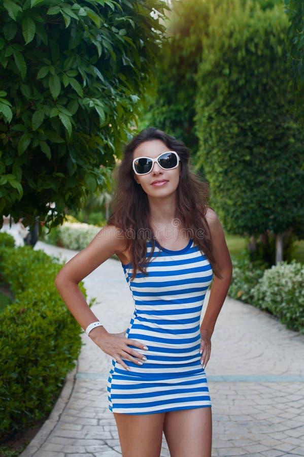 Härlig ung kvinna i solglasögon som poserar i parkera arkivfoto