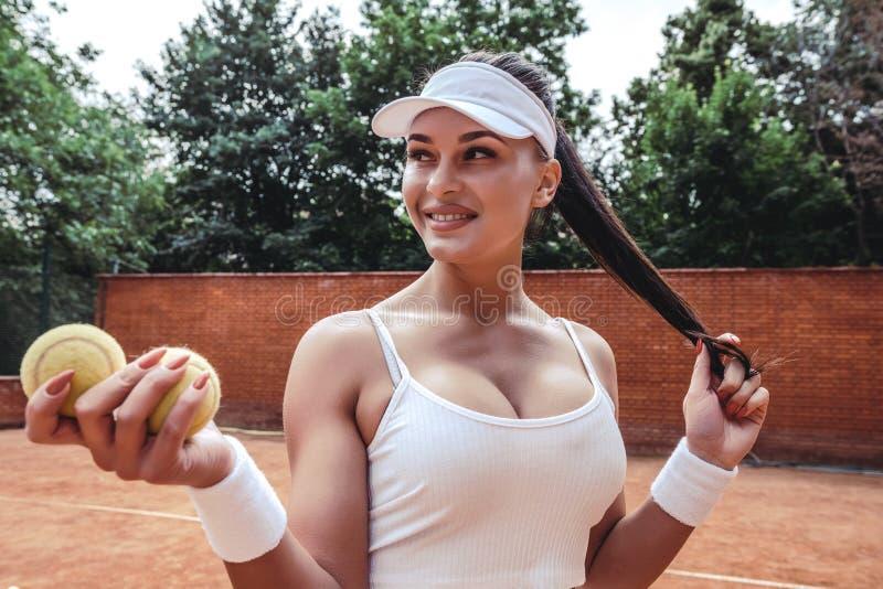 Härlig ung kvinna i sportkläder som bort ler och ser royaltyfria bilder