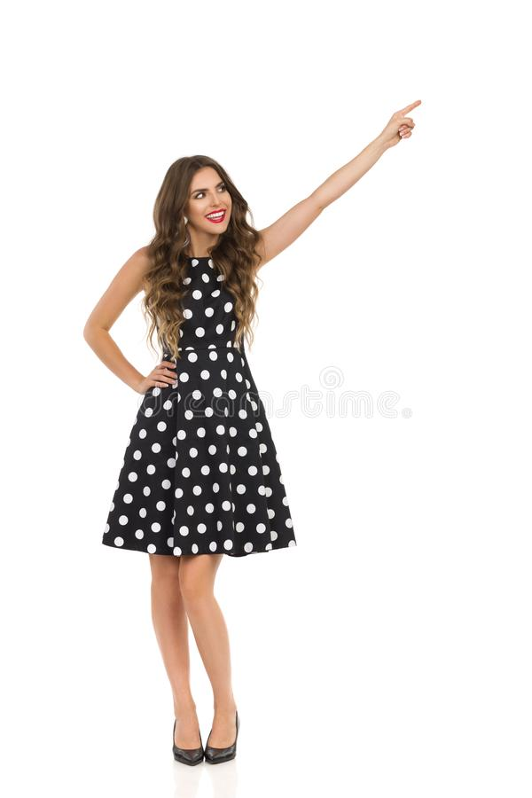 Härlig ung kvinna i svart coctailklänning i polkan Dots And High Heels Is som bort pekar och ser fotografering för bildbyråer
