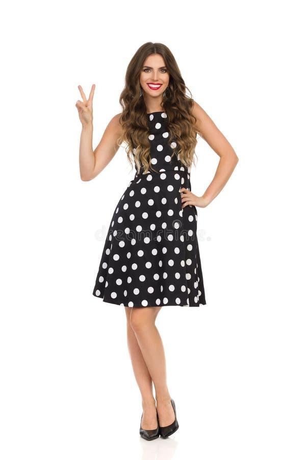 Härlig ung kvinna i svart coctailklänning i polkan Dots And High Heels Is som visar fredhandtecknet fotografering för bildbyråer