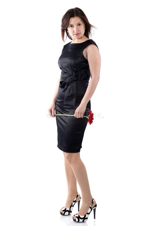 Härlig ung kvinna i svart klänning med gerberablomma, fullt b royaltyfria bilder