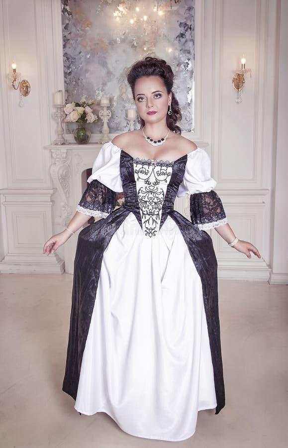 Härlig ung kvinna i svartvit medeltida klänning royaltyfri foto