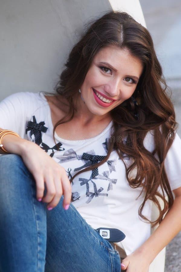 Härlig ung kvinna i t-skjorta sammanträde nära en grå vägg arkivbilder