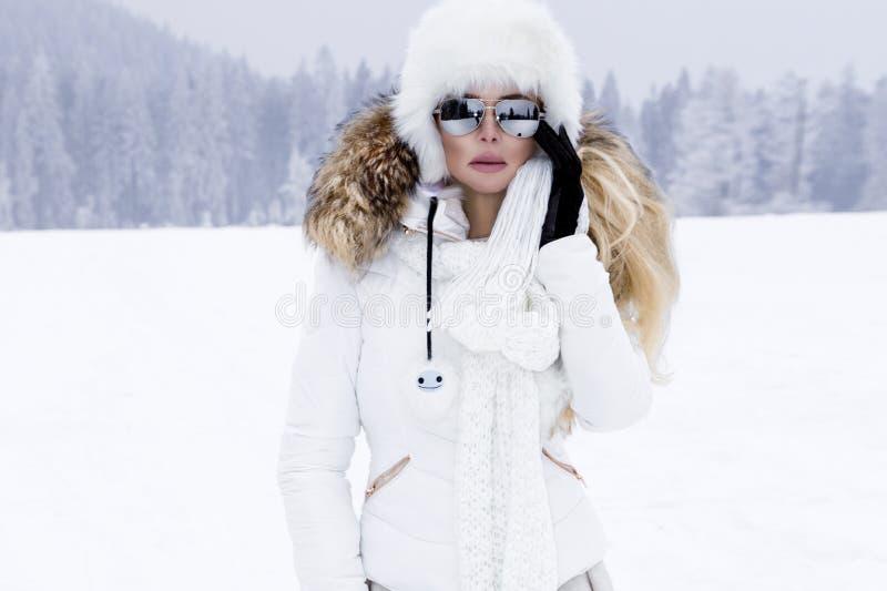 Härlig ung kvinna i vinterkläder och att stå på snön och i bakgrunden royaltyfri bild