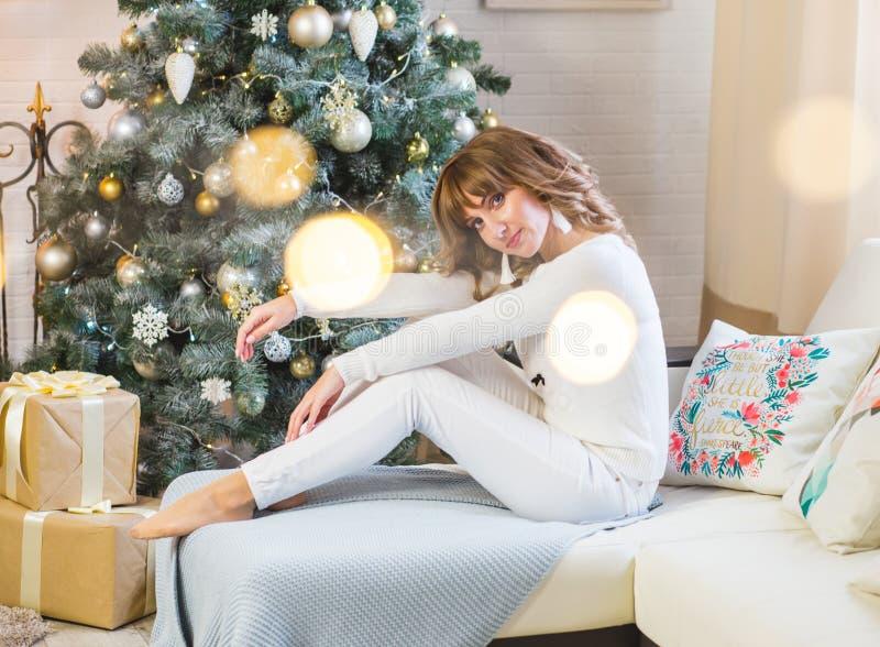 Härlig ung kvinna i vit med stora julklappar arkivbilder