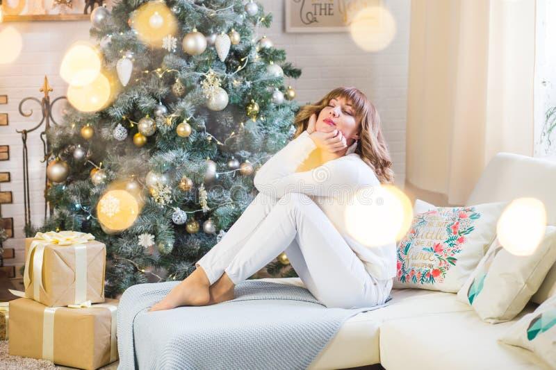 Härlig ung kvinna i vit med stora julklappar arkivfoto