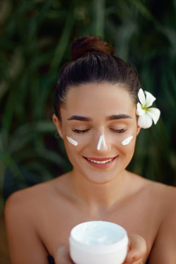 Härlig ung kvinna med att fukta kräm på framsida Kosmetisk kräm för flickainnehavflaska Kvinnlig applicerande lotion på hud skida royaltyfri bild