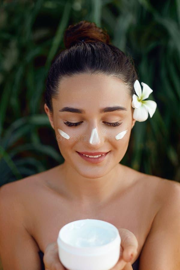 Härlig ung kvinna med att fukta kräm på framsida Kosmetisk kräm för flickainnehavflaska Kvinnlig applicerande lotion på hud skida royaltyfri fotografi
